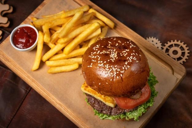 Вид сверху. бургер из говядины подается с картофелем фри на декоративной деревянной доске в томатном соусе с деревянными декоративными элементами.
