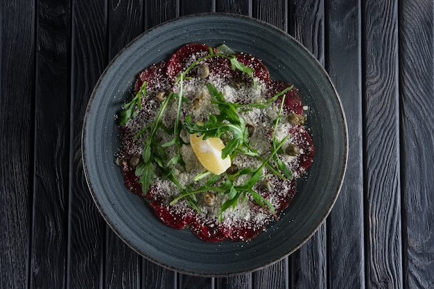 Top view of beef carpaccio with grated cheese, capers, lemon and ruccola
