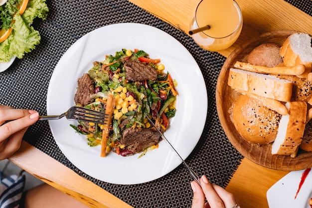 Вид сверху салат из говядины на гриле с помидорами, кукурузой, огурцом, салатом и хлебной палочкой на тарелке