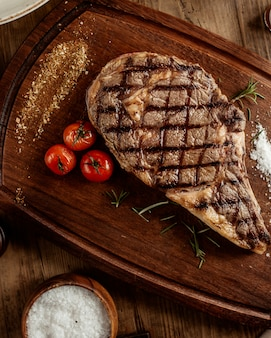 Top view of beef steak with salt herbs and cherry tomato served on board