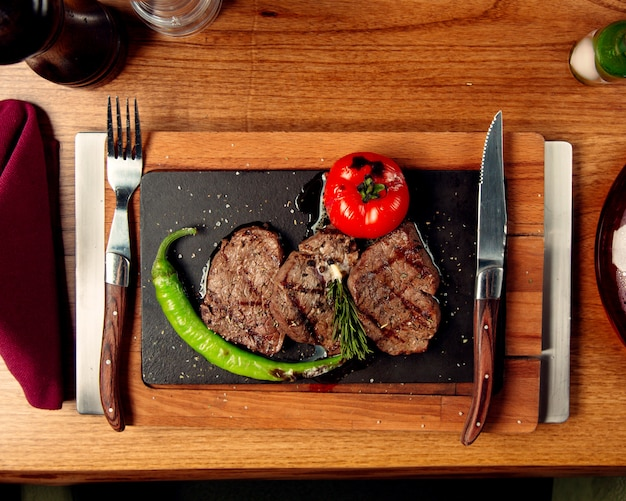 Top view of beef steaks served with grilled tomato and pepper