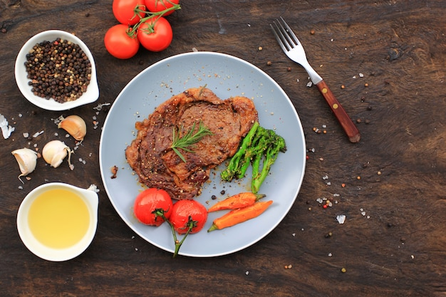 Top view of beef steaks with rosemary and roast vegetables, food meat or barbecue