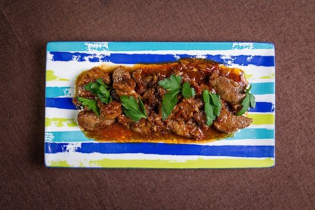 스트라이프 접시에 허브 소스와 함께 상위 뷰 쇠고기