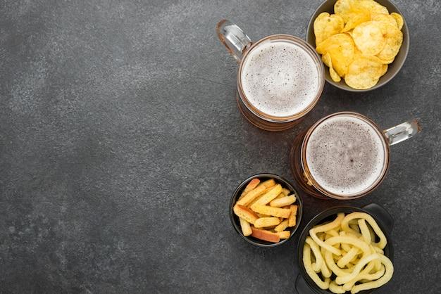 Вид сверху пиво и закуски на фоне штукатурки