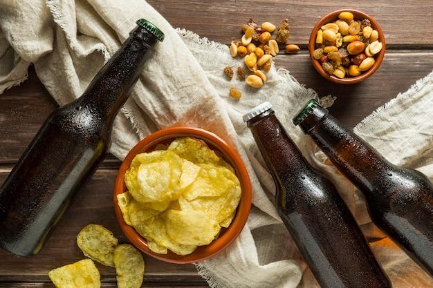 Vista dall'alto di bottiglie di birra con patatine e noci