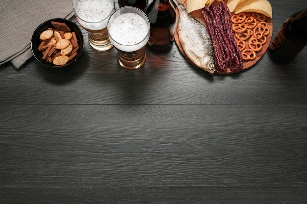 Top view beer glass and bottle with food platter with copy space