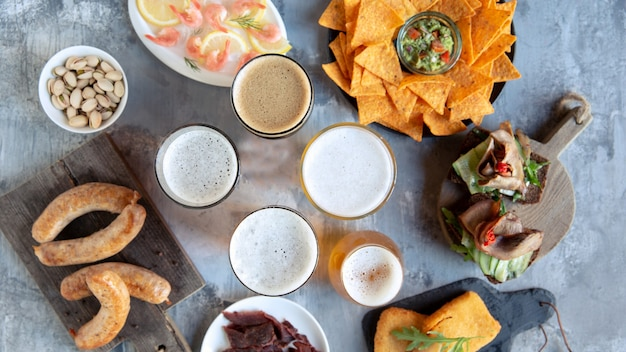 Top view of beer glasses with foam on top and delicious snacks. sausages and sauces, chips, meat, shrimp with lemon.