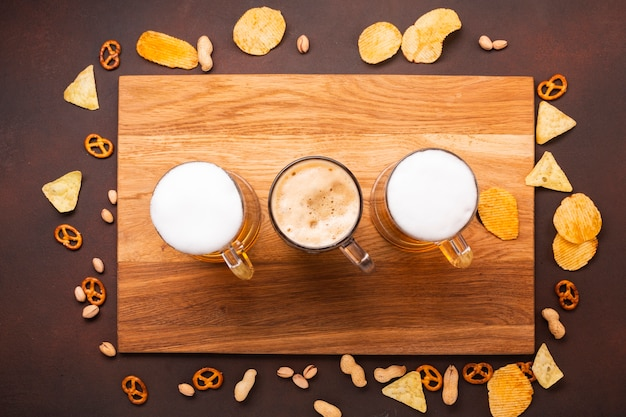Top view beer with snacks on cutting board