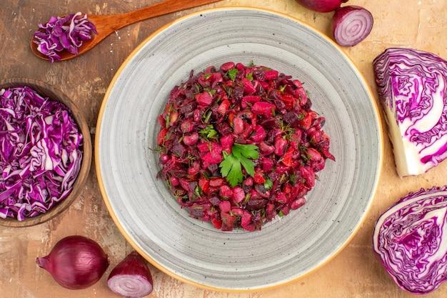 Insalata di barbabietola vista dall'alto condita con prezzemolo su un piatto di cipolle rosse, cavolo tritato e altre verdure fresche su uno sfondo di legno