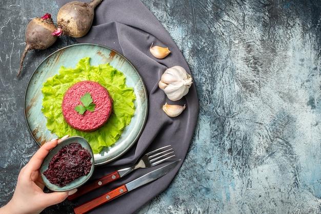 접시에 있는 상위 뷰 비트 샐러드 마늘 사탕무는 회색 테이블에 여성 손으로 보라색 목도리를 넣은 작은 그릇에 강판된 사탕무