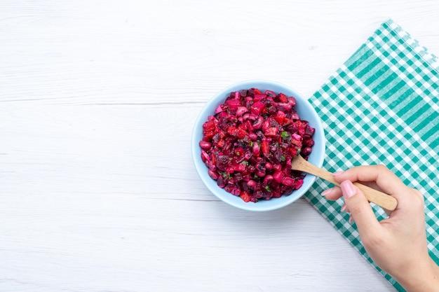 Vista dall'alto di insalata di barbabietole a fette con verdure all'interno del piatto blu su bianco, salute del pasto alimentare vitamina verdura insalata