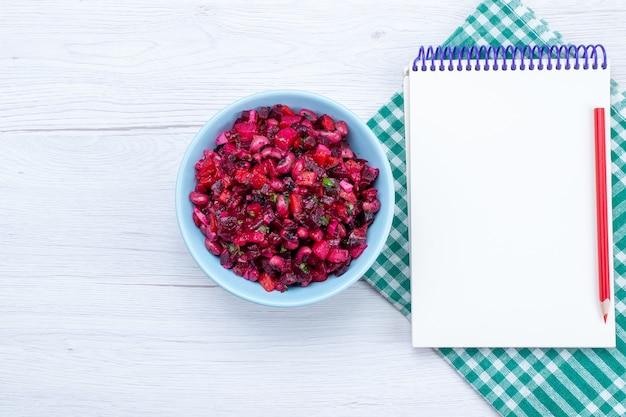 Vista dall'alto di insalata di barbabietole a fette con verdure all'interno del piatto blu con blocco note sulla scrivania leggera, salute del pasto di cibo vegetale insalata