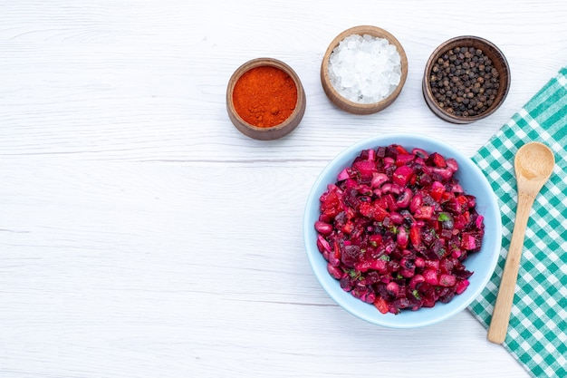 Vista dall'alto di insalata di barbabietole a fette con verdure all'interno del piatto blu con condimenti sulla scrivania leggera, insalata di salute pasto cibo vitamina vitamina