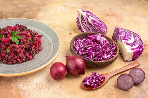 Insalata di barbabietole vista dall'alto su un piatto di ceramica con cipolle rosse e una ciotola di cavolo rosso tritato su fondo di legno