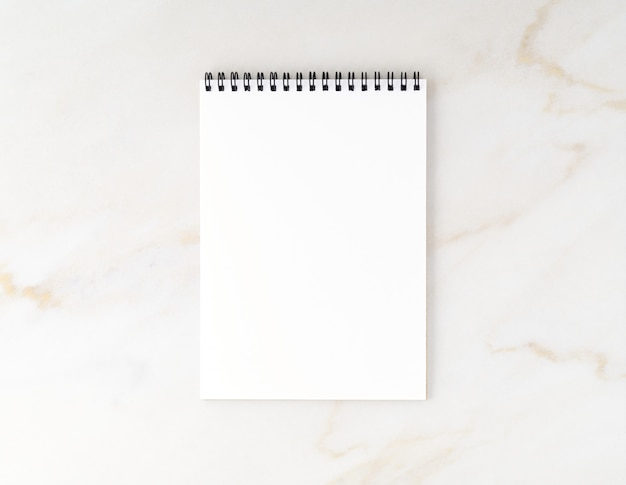 Top view of beige marble desktop with notepad. mock up, empty space