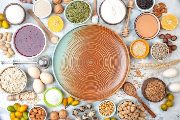 Vista dall'alto ciotole rotonde beige con marmellata di miele arachidi chicchi di grano semi di sesamo semi di zucca noci uova di quaglia cumcuats