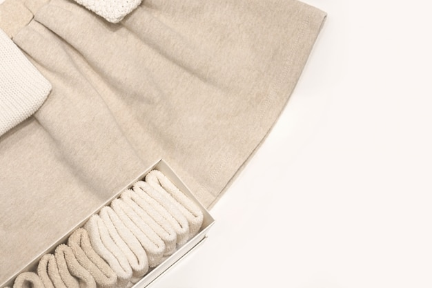 Top view on a beige skirt, sweaters and socks made from natural fabrics that lie on the table