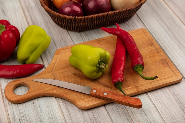 Top view of bell and chili peppers on a wooden kitchen board with knife with onions on a bucket on a grey wooden wall