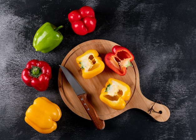 Top view bell pepper pepper with knife on wooden cutting board on black stone  horizontal