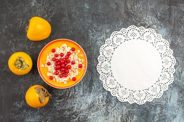 Top view of berries the appetizing berries in the bowl persimmons lace doily