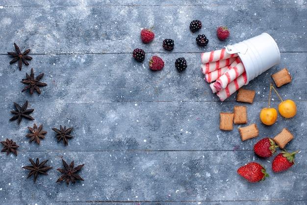 Vista dall'alto di frutti di bosco e biscotti con caramelle rosa stick sulla scrivania luminosa, biscotto ai frutti di bosco