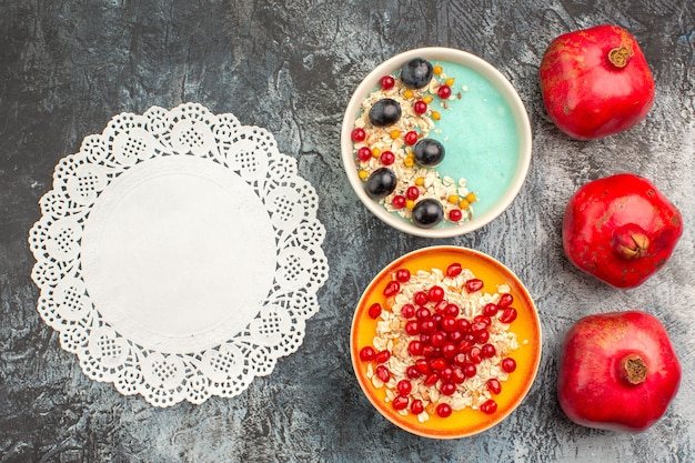 Top view of berries bowls of oatmeal grapes red currants three pomegranates lace doily