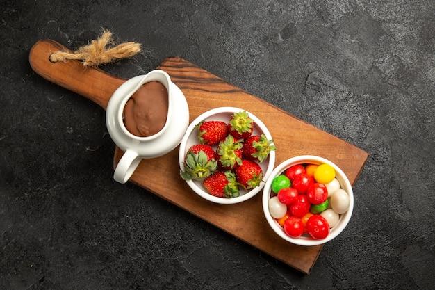 Вид сверху ягод, мисок шоколадного соуса, конфет и клубники на деревянной разделочной доске на темном столе