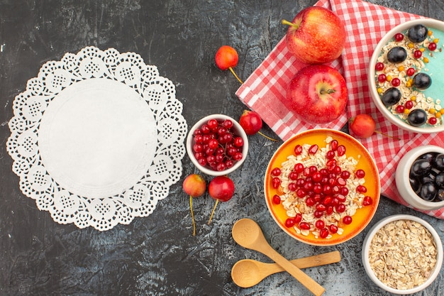 Top view berries bowls of red currants cherries grapes apples pomegranate oatmeal lace doily