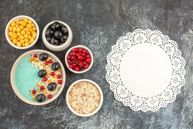 Top view berries bowls of red currants grapes oatmeal yellow candies lace doily