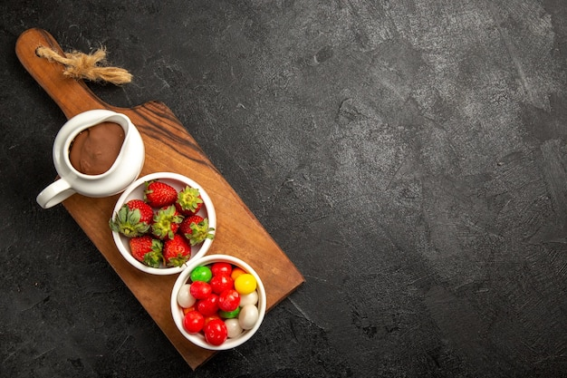 Top view berries bowls of sweets chocolate cream and strawberries on the wooden cutting board on the left side of the dark table