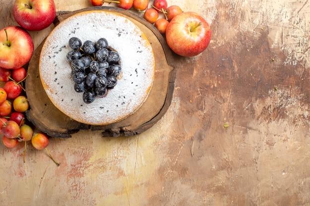 Vista dall'alto di frutti di bosco una torta con l'uva sulle mele tavola di legno e frutti di bosco