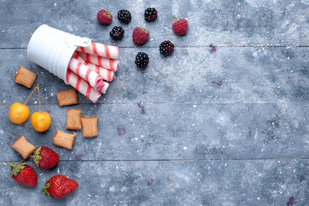 Top view of berries and cookies with pink stick candies on bright desk, fruit berry cookie