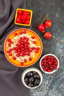 Top view berries oatmeal seeds of pomegranate red currants cherries grapes on the tablecloth