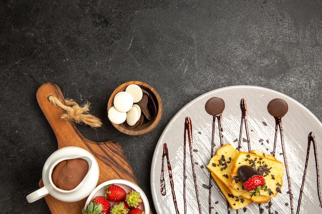 キッチンボード上のチョコレートとイチゴのボウルの横にあるケーキチョコレートとイチゴのトップビューベリープレート 無料写真