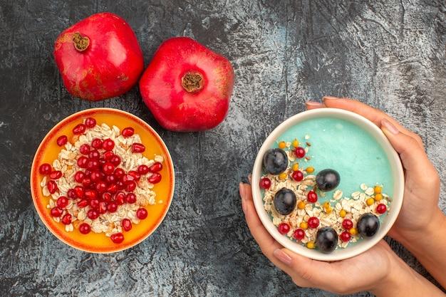 손에 딸기 오트밀 석류 그릇의 상위 뷰 열매 석류 오트밀 씨앗