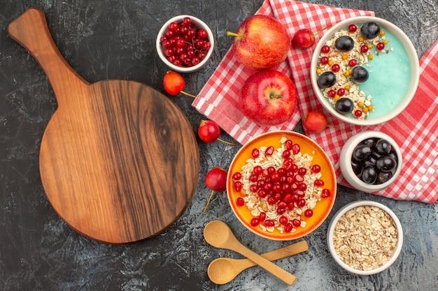 Vista dall'alto di frutti di bosco cucchiai mele bacche colorate farina d'avena melograno il tagliere