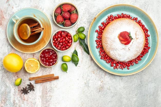 Vista dall'alto bacche e tè una tazza di tè marmellata bacche bastoncini di cannella la torta con le fragole