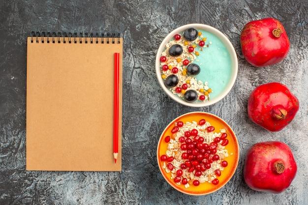 상위 뷰 열매 오트밀 포도 붉은 건포도 석류 오트밀 노트북 연필의 두 그릇
