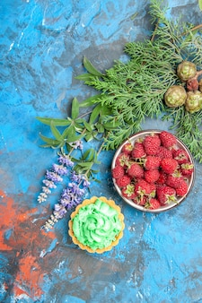 Top view of berry bowl, small tart and tree branches on blue surface