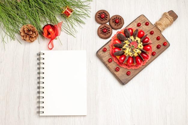 Torta di bacche vista dall'alto sul tagliere biscotti e foglie di pino con i giocattoli di natale e un taccuino sul terreno di legno bianco