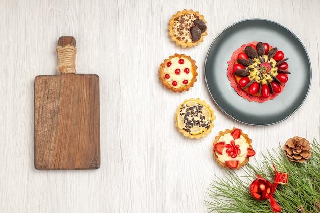 회색 접시의 상위 뷰 베리 케이크와 오른쪽 상단에 타르트, 오른쪽 하단에 소나무 잎, 흰색 나무 바닥의 왼쪽에 도마
