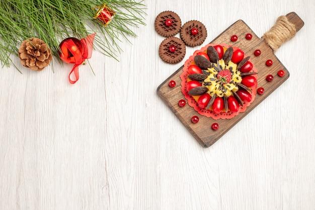 Вид сверху ягодный торт на разделочной доске печенье и листья сосны с елочными игрушками на белой деревянной земле