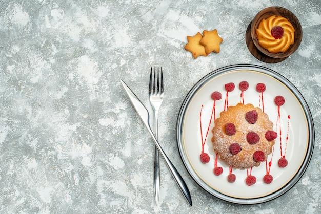 Вид сверху ягодный торт на белой овальной тарелке, печенье в миске, скрещенные вилка и обеденный нож на серой поверхности свободное пространство