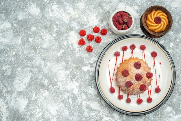 Вид сверху ягодный торт на белой овальной тарелке с малиновым бисквитом на серой поверхности свободного пространства