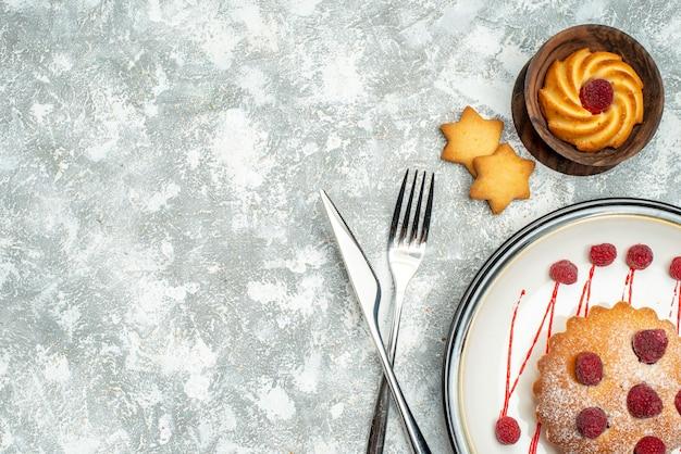 白い楕円形のプレートの上のビューベリーケーキは、灰色の表面の空きスペースにフォークとディナーナイフを交差させました
