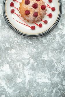 회색 표면 복사 장소에 흰색 타원형 접시에 상위 뷰 베리 케이크