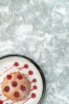 灰色の表面の自由空間に白い楕円形のプレート上の上面図ベリーケーキ
