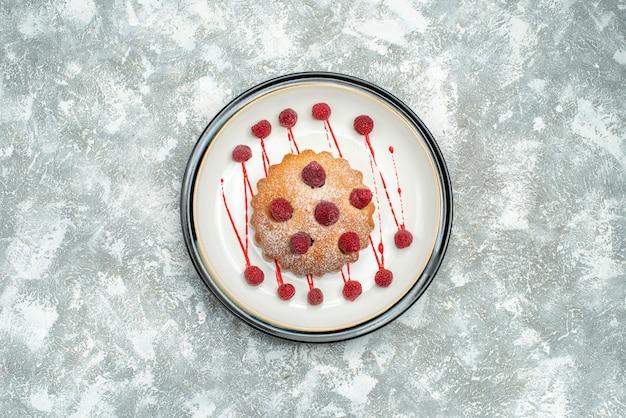 복사 공간 회색 표면에 흰색 타원형 접시에 상위 뷰 베리 케이크