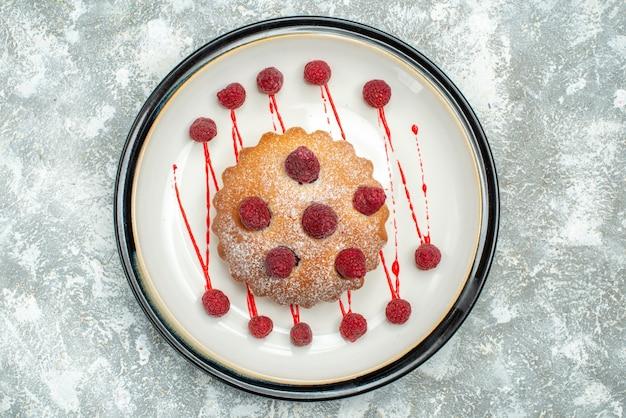 Вид сверху ягодный торт на белой овальной тарелке на серой поверхности