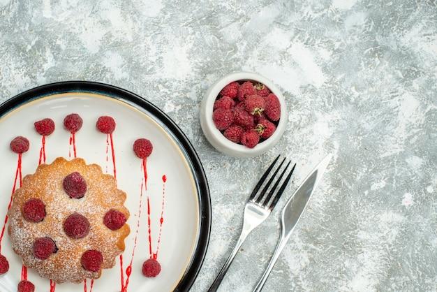 ボウルフォークの白い楕円形のプレートラズベリーと灰色の表面の空きスペースにディナーナイフの上面図ベリーケーキ